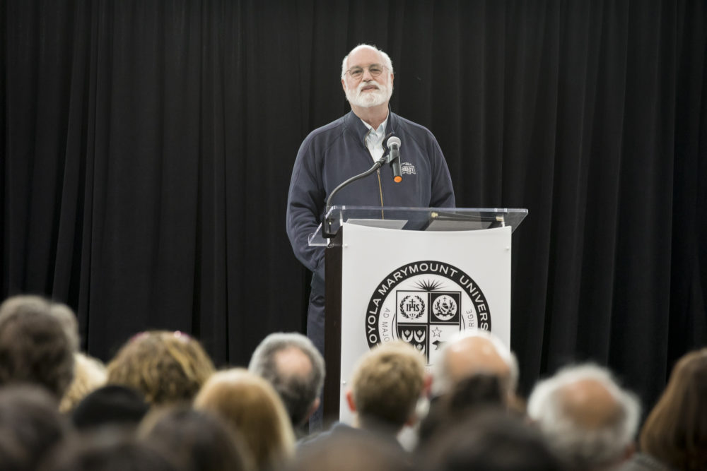 Father Gregory Boyle in front of a podium