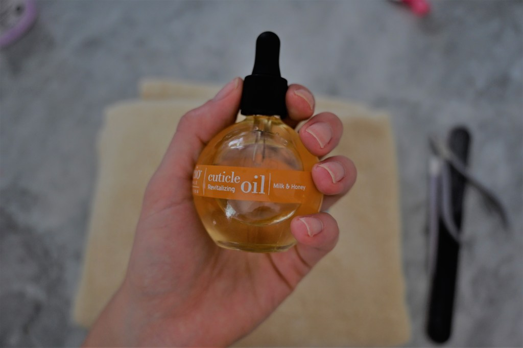 Lifestyle blogger Maria Munoz of Bella Style Living with cuticle oil for manicure at home