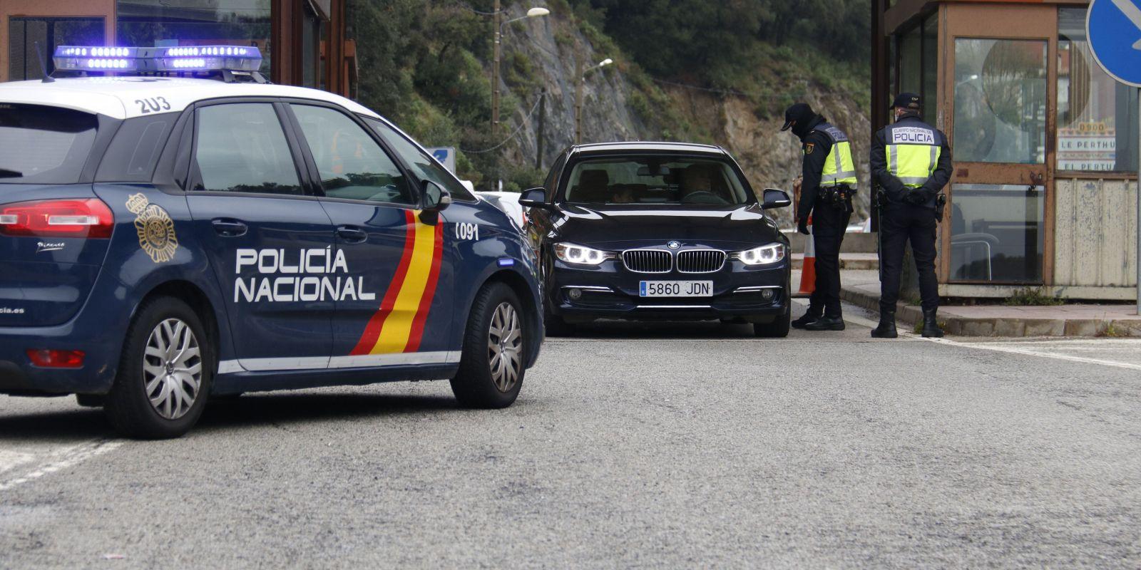 Dos agents de la Policia Nacional fent un control a un turisme que vol creuar la frontera | ACN