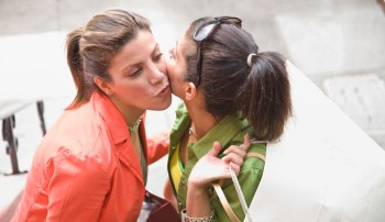 Middle Eastern women greeting each other with kiss