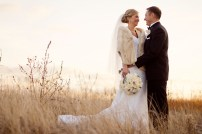 fall-bride-and-groom-pose-outside-fur-shrug-ivory-bridal-bouquet.original