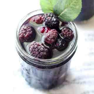 mason jar filled with blackberry sweet tea and frozen blackberries