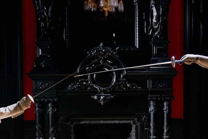 people holding silver metal rod near black fireplace