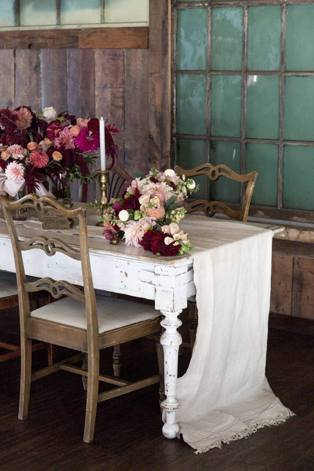 Long wedding tablescape with burgundy centerpieces - Photography: Szu Designs, Inc