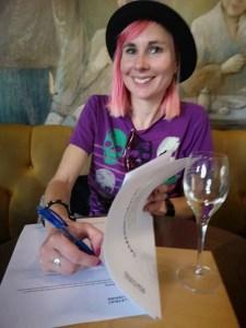 FörfattarenLouise Halvardsson i rosa hår, lila tröja och svart hatt skriver under författaravtal vid ett kafébord.