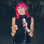 Författaren och estradpoeten Louise Halvardsson i rosa hår och mikrofon i handen.