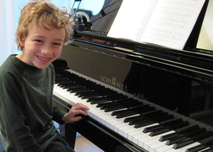Young boy studying piano lessons