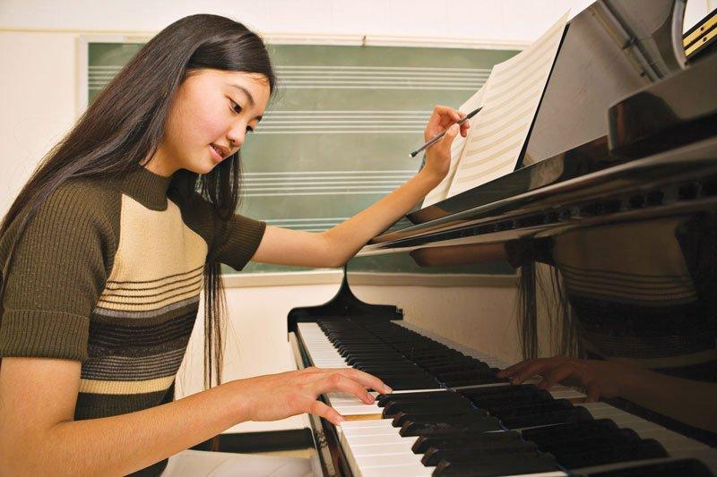 Asian girl studying piano