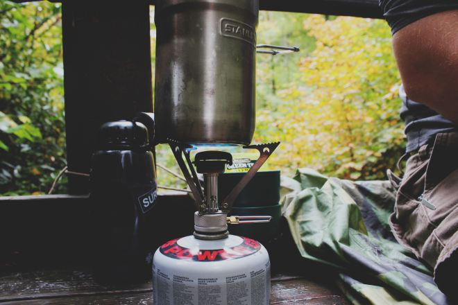 A lit burner underneath a metal pot next to a man sitting in his campsite, for first family camping trip. Photo by Brandi Redd on Unsplash