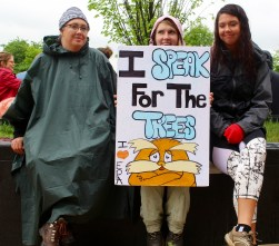 Three women hold their Lorax inspired sign at the start of the march. Photo by Lauren Anikis 4/22/17
