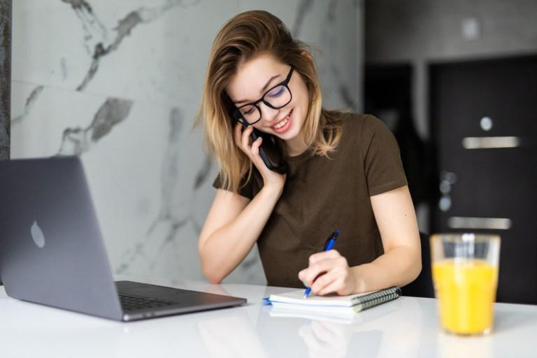 mulher-jovem-sentada-mesa-cozinha-fala-sobre-dinheiro-ao-celular.jpg