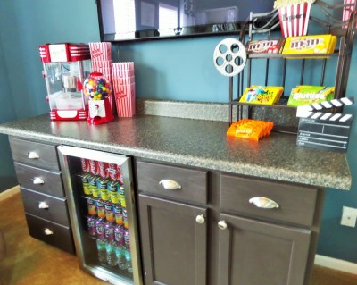 Home Theater Ideas Decor Concession Stand Popcorn Maker Popper Mini Fridge Candy M&Ms Skittles Sour Patch Gum Balls Coke Coca Cola Minute Maid Buffet Cabinets Popcorn Bucket