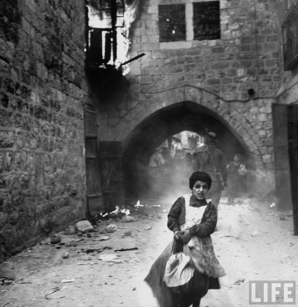 Jewish girl, Rachel Levy, 7, fleeing from street w. burning bldgs. as the Arabs sack Jerusalem after its surrender. May 28, 1948. John Phillips