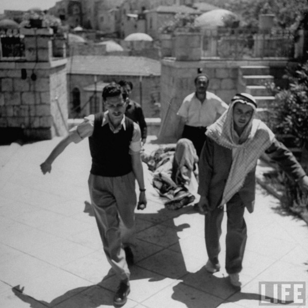 Wounded Arab Legionnaire is carried by civilian volunteers. Jerusalem. May 1948