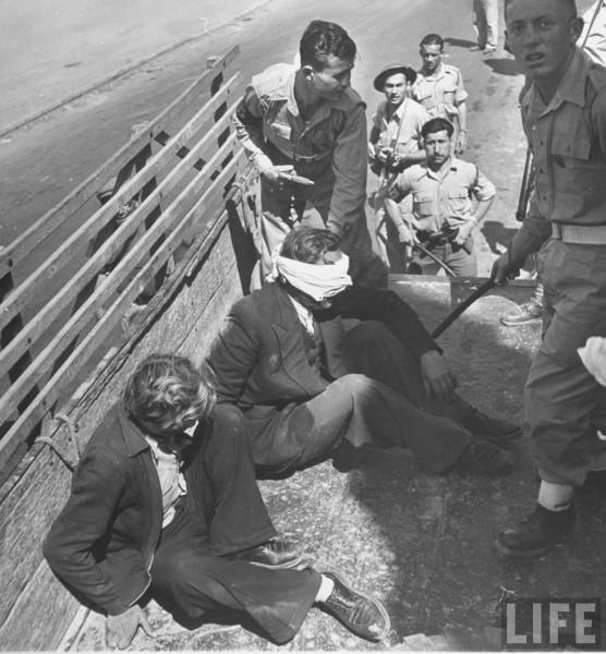Jewish troops blindfolding Polish adventurers doing sabotage for Arabs. May 1948. John Phillips