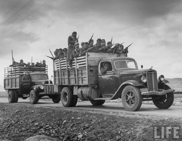 Arab soldiers with rifles being transported in military vehicles. March 1948. John Phillips