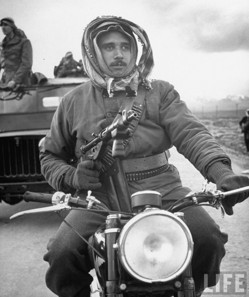 Arab soldier with rifle riding on a motorcycle. March 1948. John Phillips