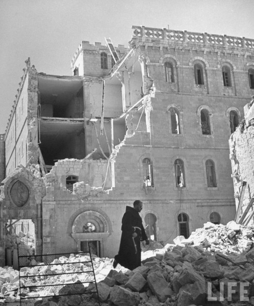 mPriest walking past the Convent of Notre Dae du France which was damaged during fighting in the city