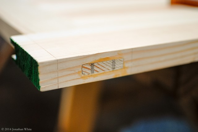 The excess tenon and wedges are sawn off.