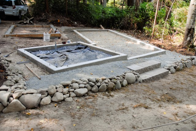 I removed the rock-wall, installed some steps, and rebuilt the wall further from the coop foundation.