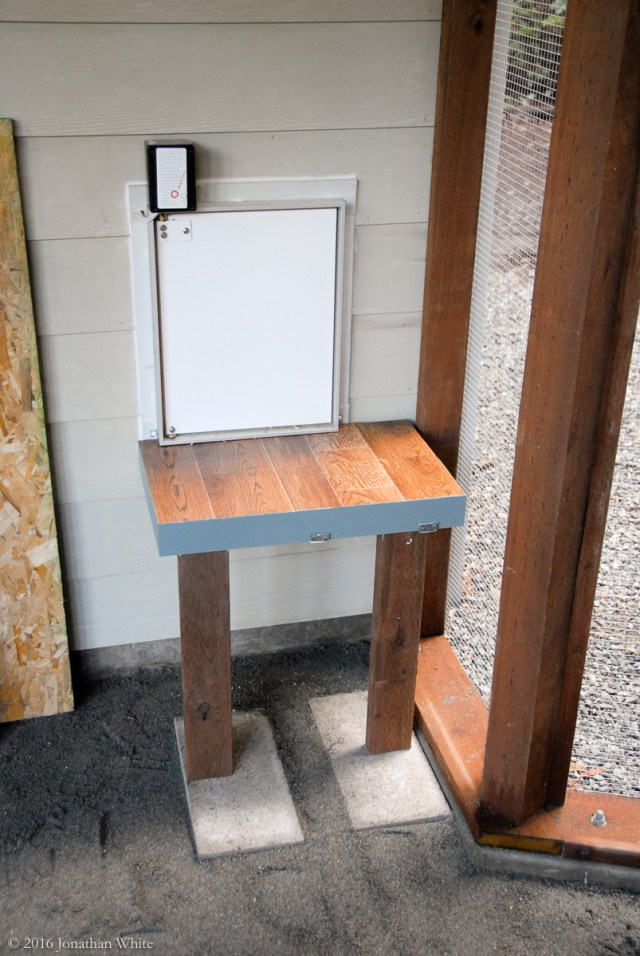The back of the platform is attached with small angle brackets. The legs just stand on the pavers.