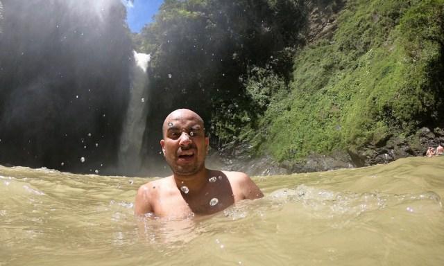 Ein Tourist badet im Backen der Tappiyah Falls und macht dabei ein Selfie