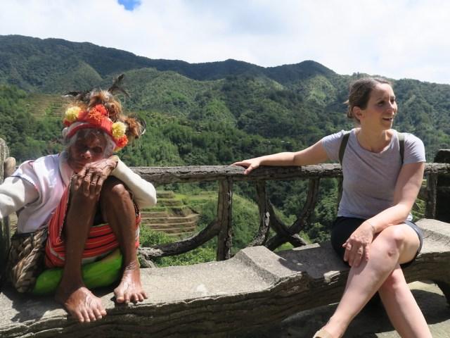 Eine europäische Touristen sitzt zusammen mit einer Einheimischen des Stammes Ifugao am Banaue Viewpoint