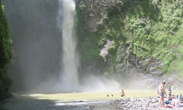 Touristen baden bei sonnigem Wetter im Becken der Tappiya Falls