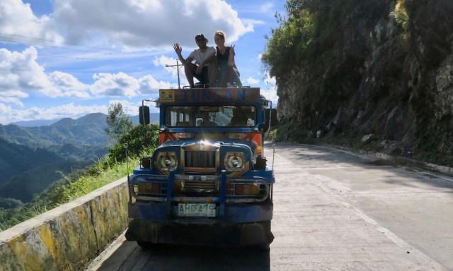 Ein Pärchen sitzt auf dem Dach eines blauen Jeepneys und winkt in die Kamera