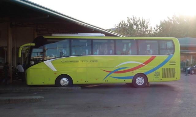 Ein grün gelber Bus von Ceres Tours steht am Bus Terminal in Cebu City