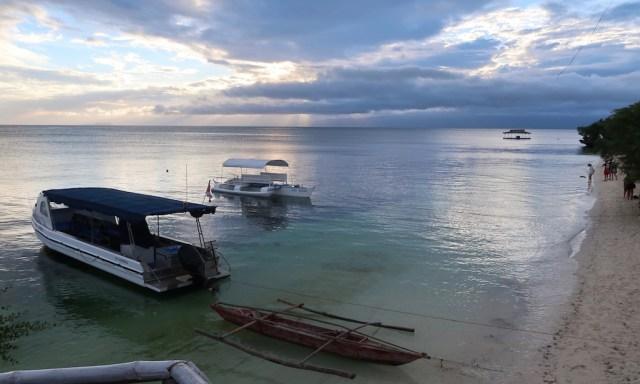 Abendstimmung am Paliton Beach wo zwei Boote im Wasser schwimmen