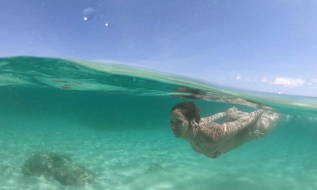 Go Pro Dome Halb Unterwasser Bild mit tauchender Frau im Türkisen Wasser
