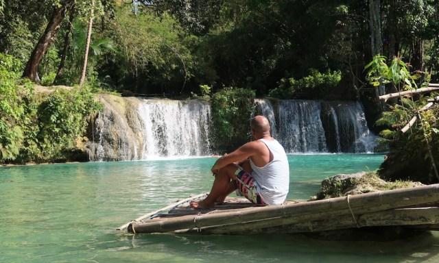 Bendja sitzt auf einem Floß und betrachtet die Cambugahay Falls