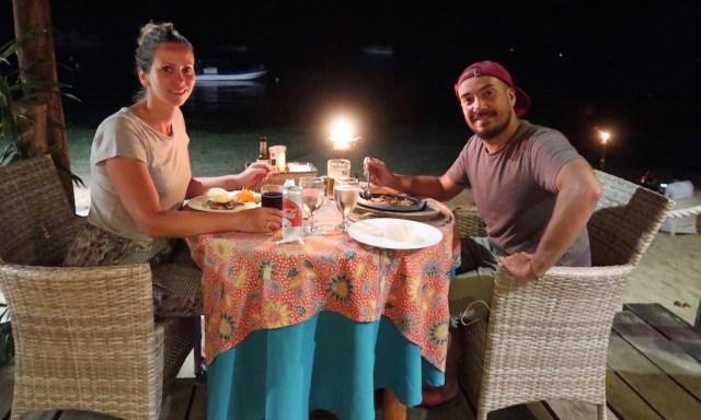 Bendja und Maus speisen an einem kleinen Tisch am Strand beim Sunset Restaurant in Siquijor