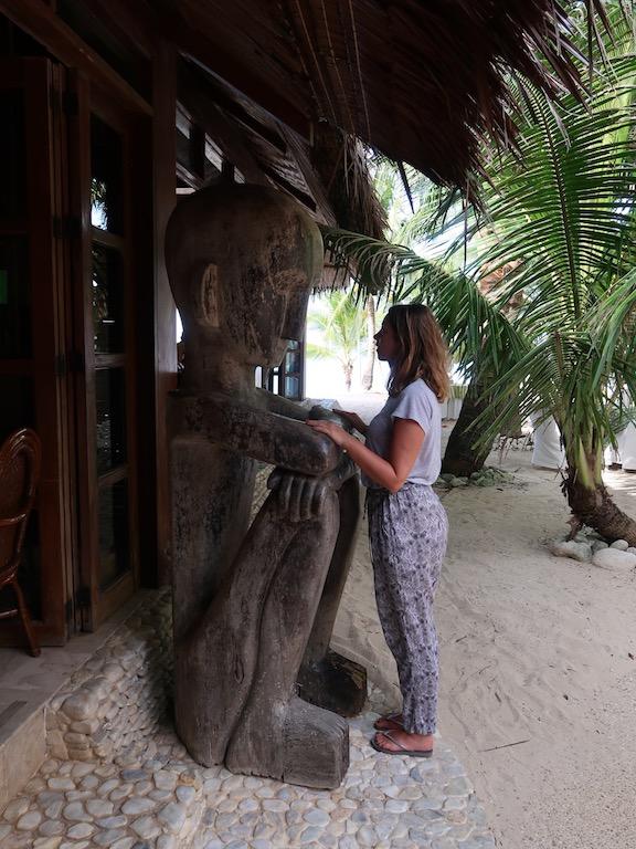 Eine Frau steht einem großen hölzernen Reisgott gegenüber