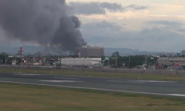 Auf der Landebahn am Flughafen Manila. Im Hintergrund schwarze Rauchschwaden eines brennenden Gebäudes
