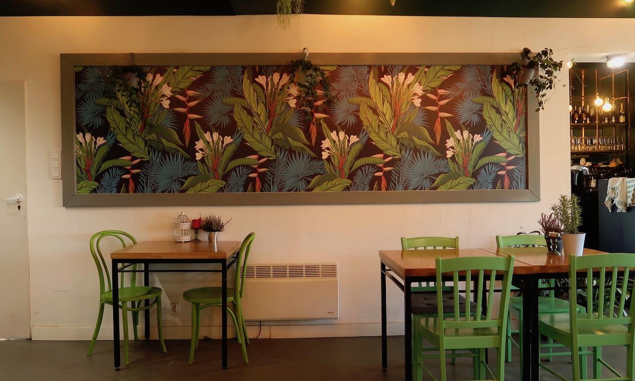 Inneneinrichtung bestehend aus grünen Holzstühlen und Planzenbild im Café Grin in Kohlberg