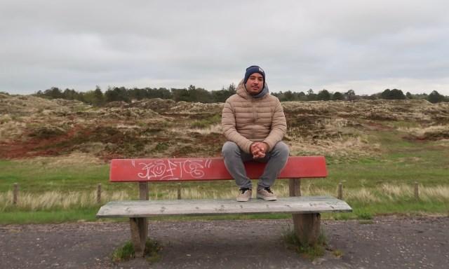 Typ mit Wollmütze sitzt auf einer Parkband auf den Deichen Sankt Peter-Ordings
