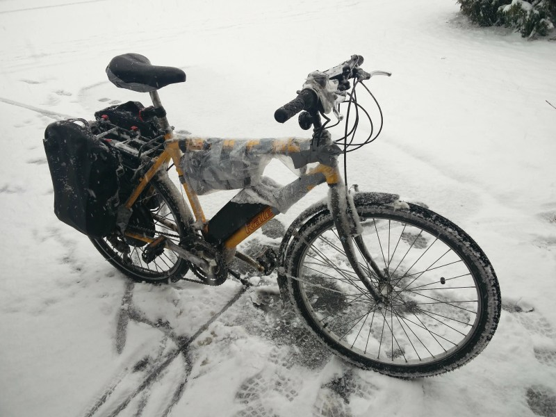 Ben's ebike, on the driveway in the snow, plastic protecting its important electronic components