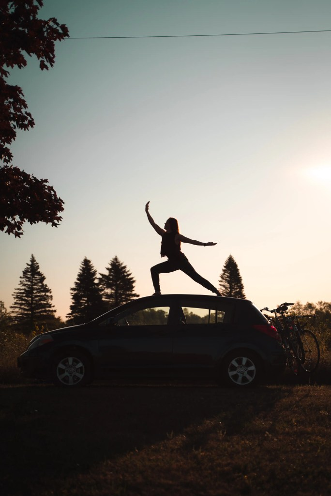 beautiful golden hour photo of Natalia in the morning light while doing a yoga pose on top of her Nissan Versa