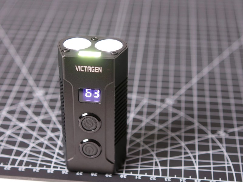 The Victagen front bike light, sitting on a backdrop filled with 1x1cm measurement squares everywhere