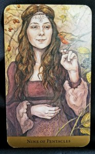 Nine of Pentacles Woman standing in the woods holding a small red-breasted bird on her finger