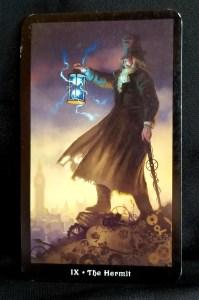 The Hermit An older man, standing on broken gear, holding a lantern