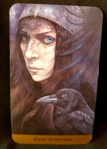 Eight of Swords - Woman dressed in a black veil with a raven next to her