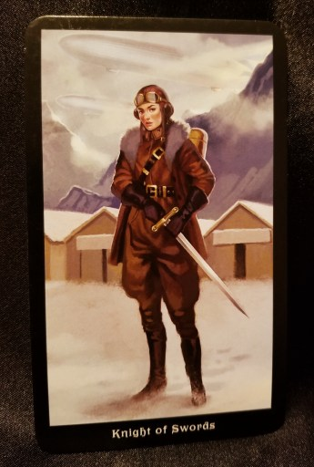 Knight of Swords- Woman with a sword at her side. An airfield is in the background.