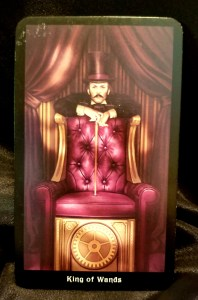 King of Wands - Man standing behind an upholstered chair, his cane resting on the seat