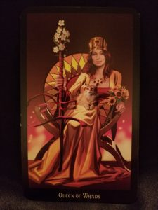 Queen of Wands - Woman sitting on a throne, a cat in her lap, holding a flowered staff