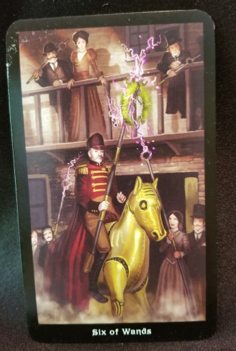 Six of Wands - Man sitting atop a mechanical ohorse carrying a wreath on a pole