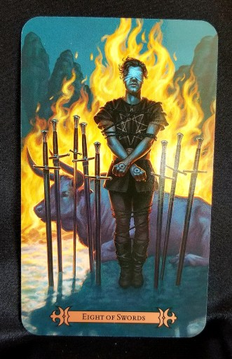 Eight of Swords - A man blinfolded and bound, stanfing in front of a fire and a bull, surrounded by swords