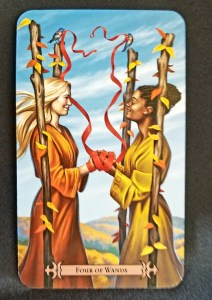 Four of Wands - Two women, their hands wrapped together with red ribbon, standing between 4 staffs